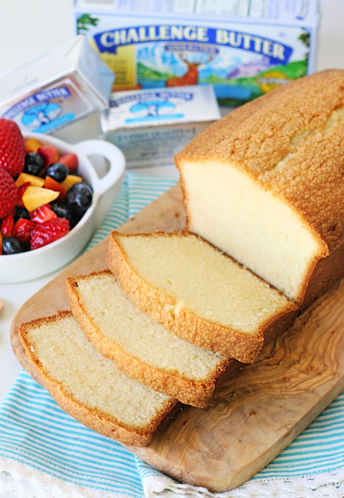 loaf pound cake on wood board with 3 slices cut sitting next to a bowl of berries.
