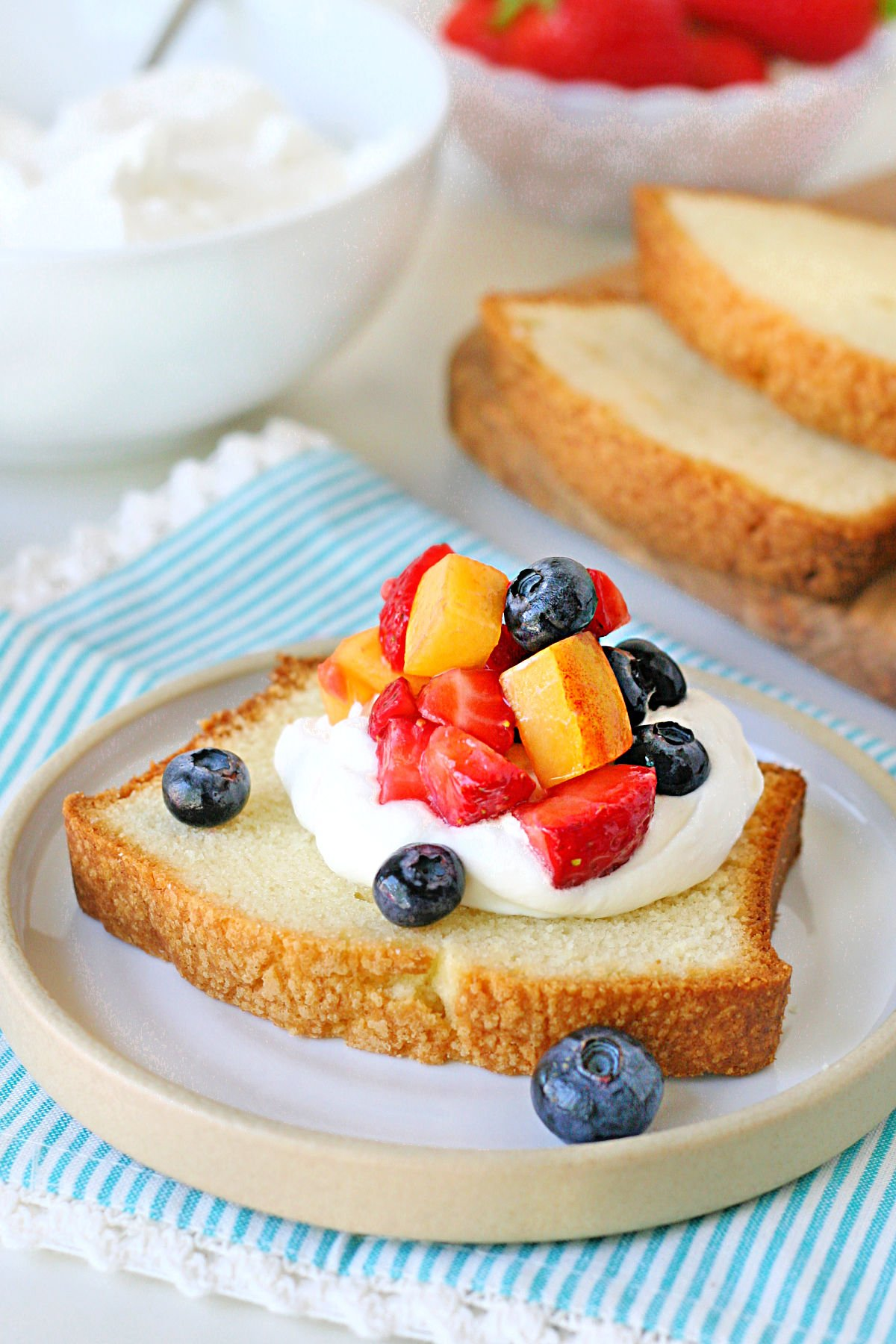 close up look at pound cake slice topped with whipped cream and fruit.