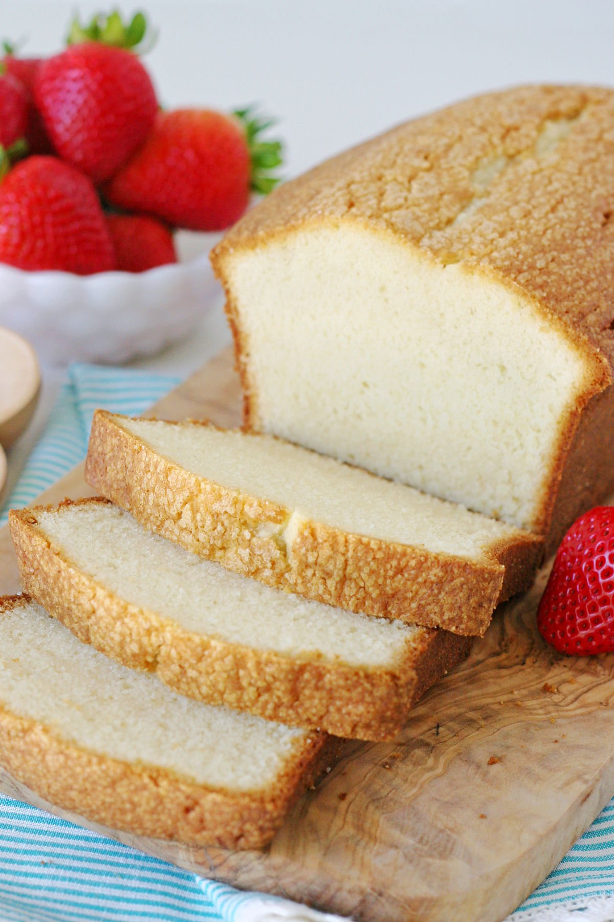 easy pound cake recipe cut up on wood board with strawberries in background.