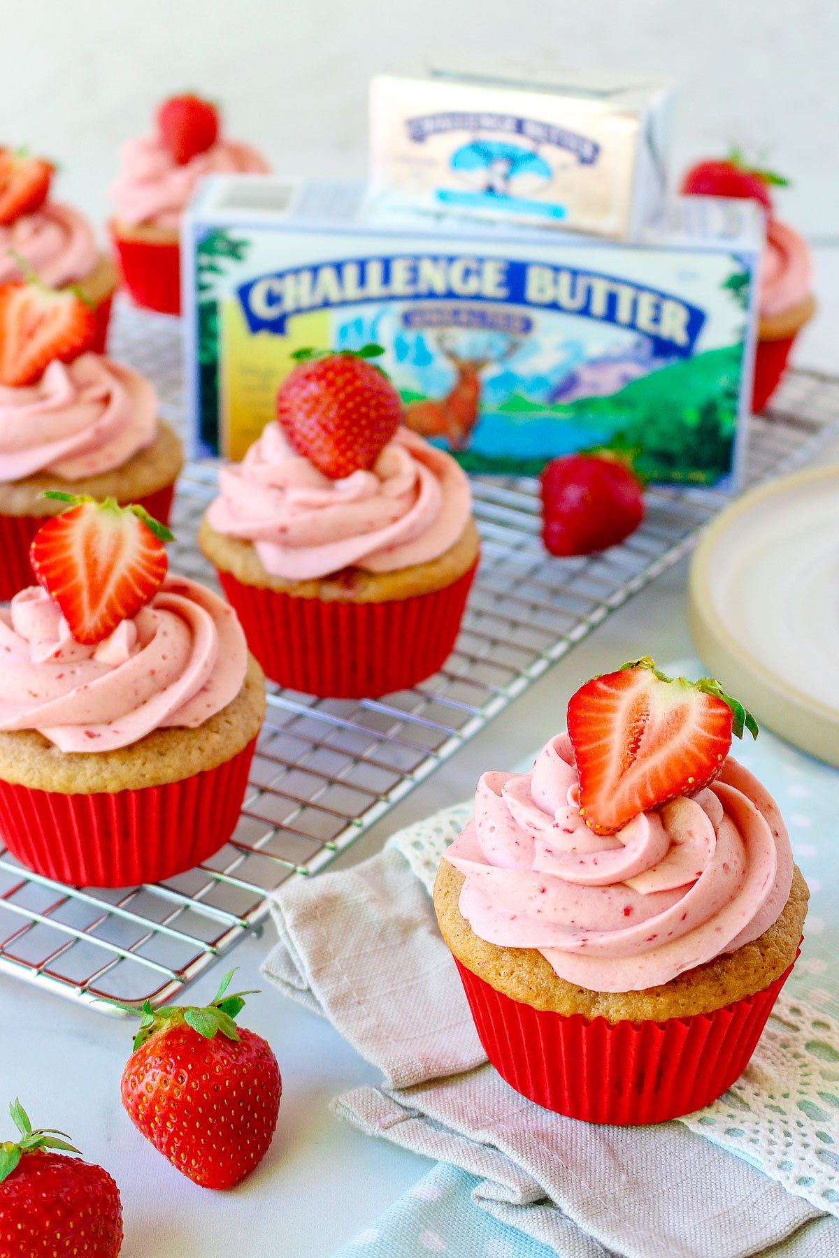 strawberry cupcakes topped with strawberry frosting with butter package in back