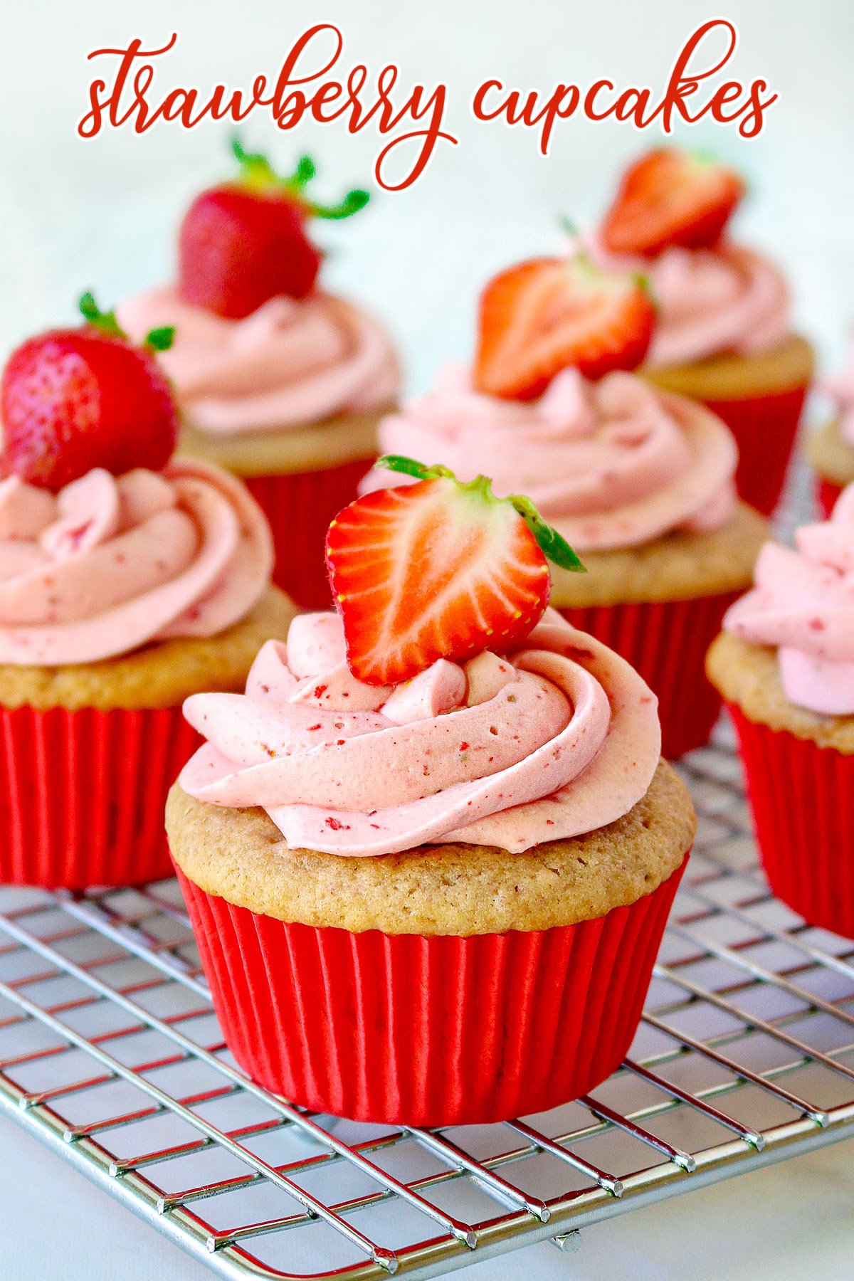 strawberry cupcake recipe on cooling rack with strawberry frosting and title overlay
