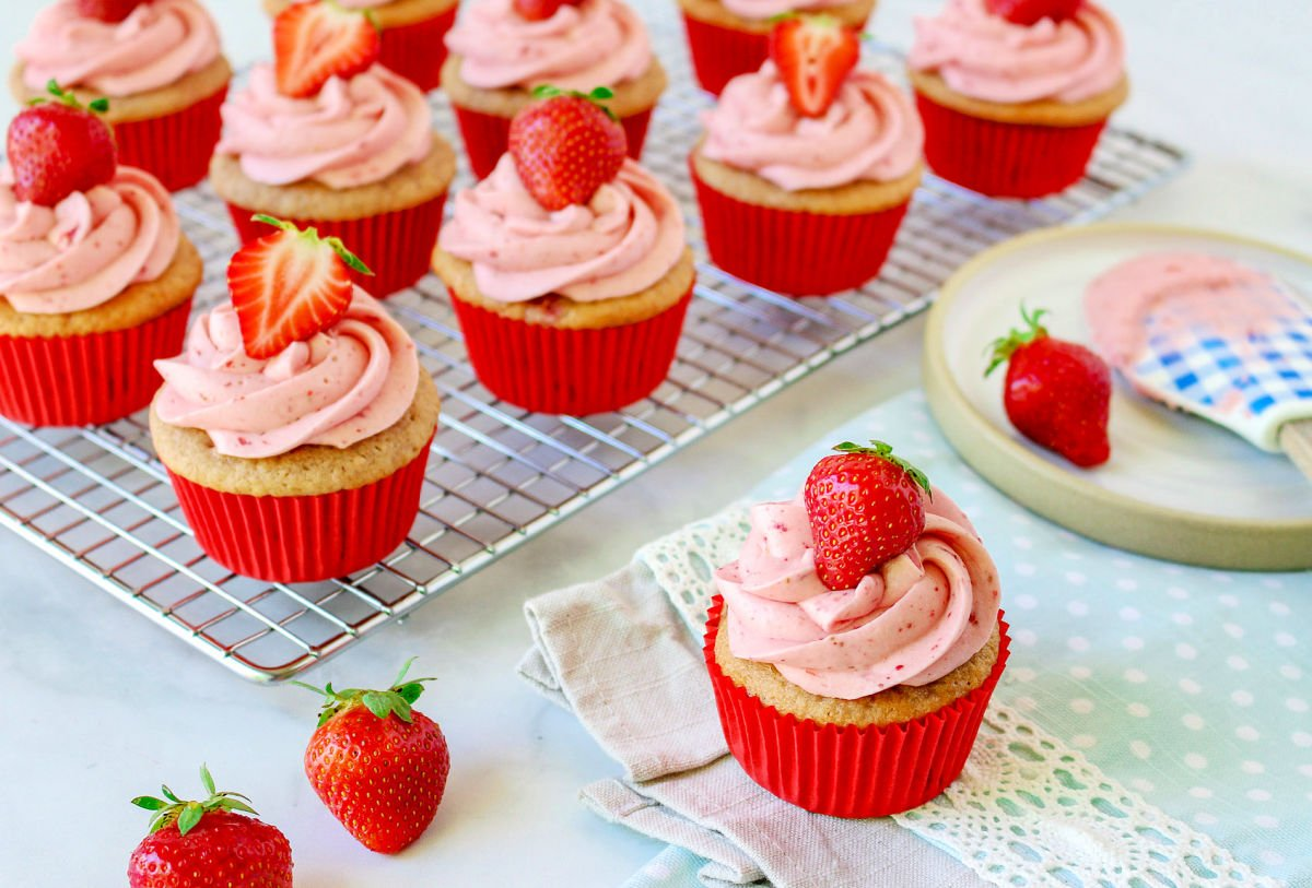 strawberry cupcakes on cooling rack with one plate