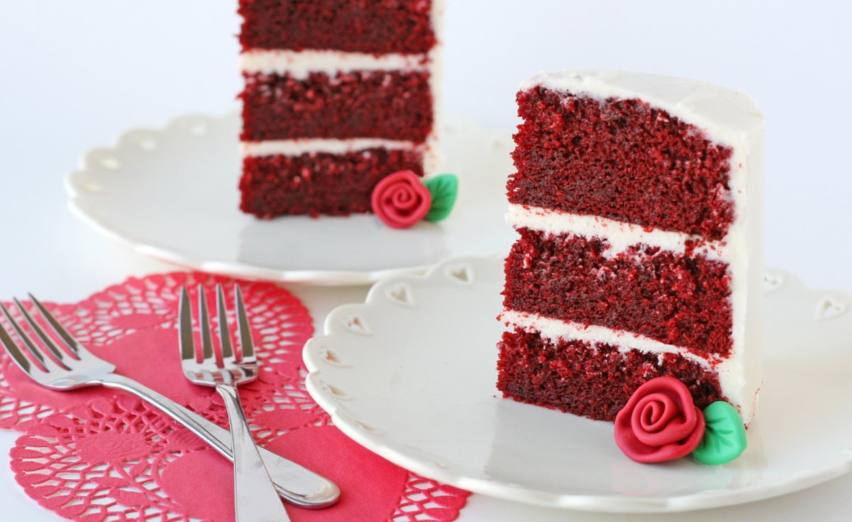 two slices of red velvet cake with fondant rose on white plate