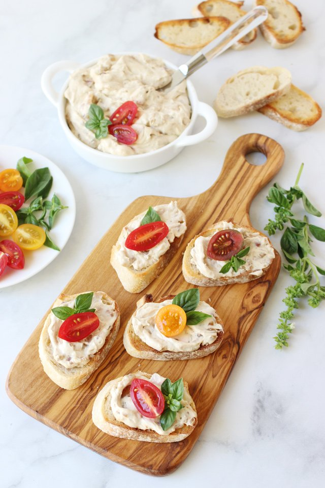 onion dip served on crostini garnished with tomato and basil