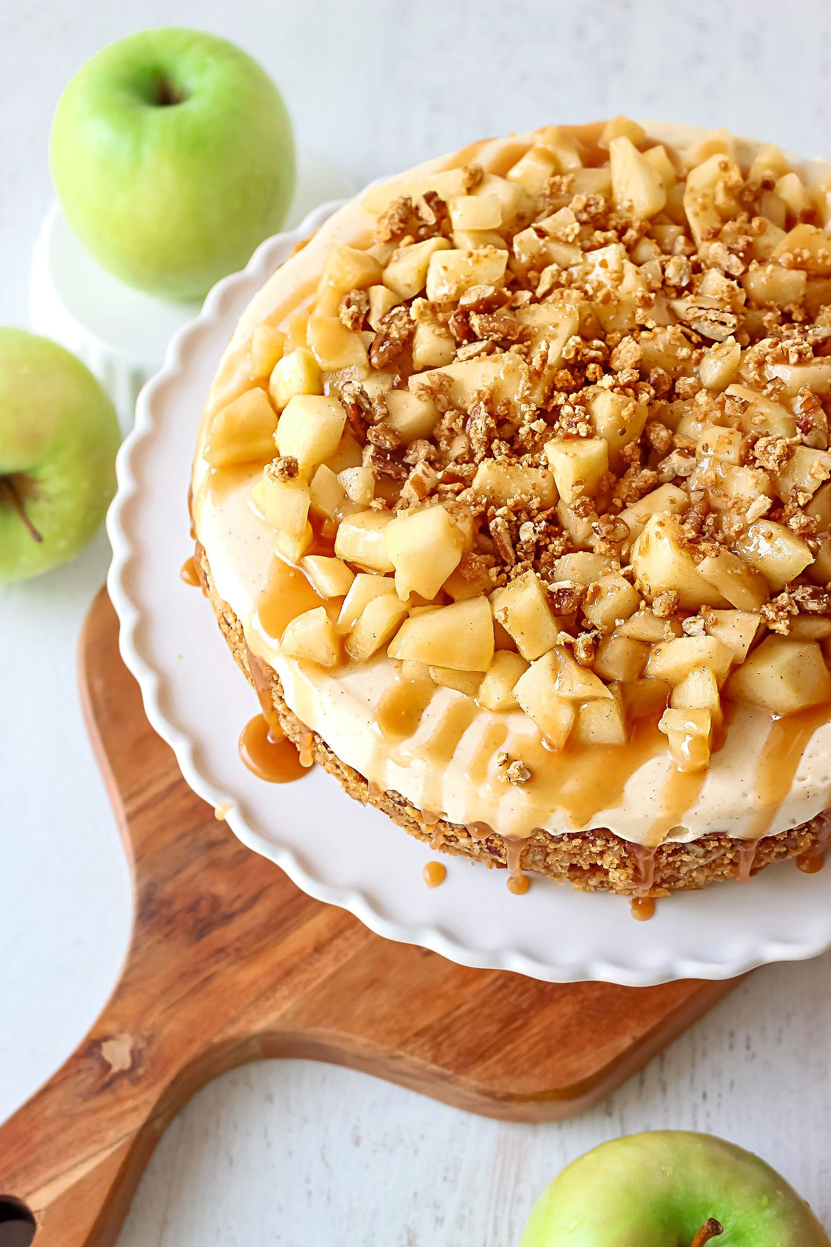 top down view caramel apple cheesecake recipe on white cake plate sitting on wood board