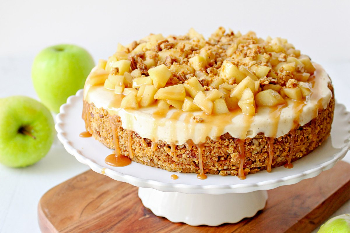 whole caramel apple cheesecake on white cake plate on wood board