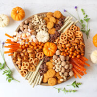 top down view of fall charcuterie board with pumpkins and fall treats