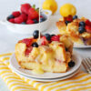 bread pudding made with fresh berries and drizzled with a lemon sauce sitting on white plate on a yellow and white striped towel.