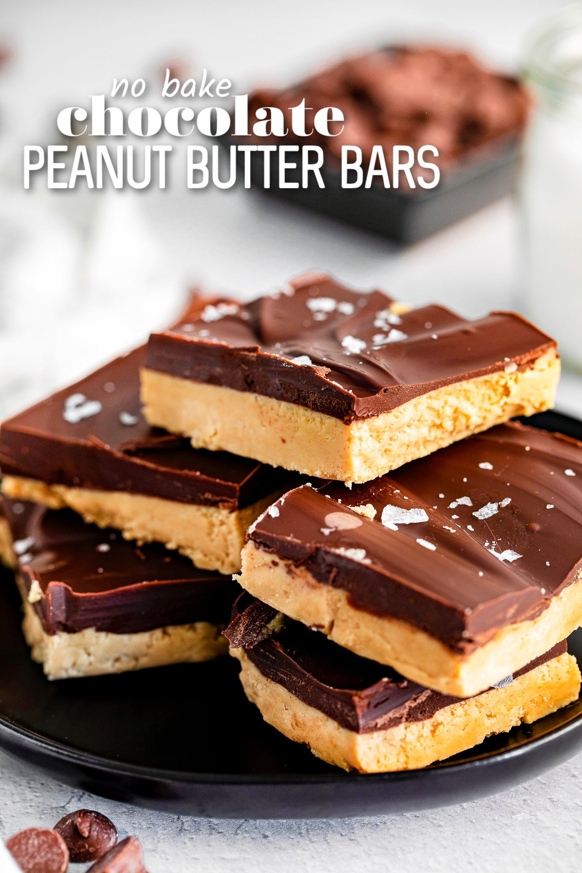 peanut butter chocolate bars stacked on black plate and sprinkled with sea salt. title overlay at top of image.