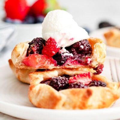 three mini berry galettes on small white plate topped with whipped cream.