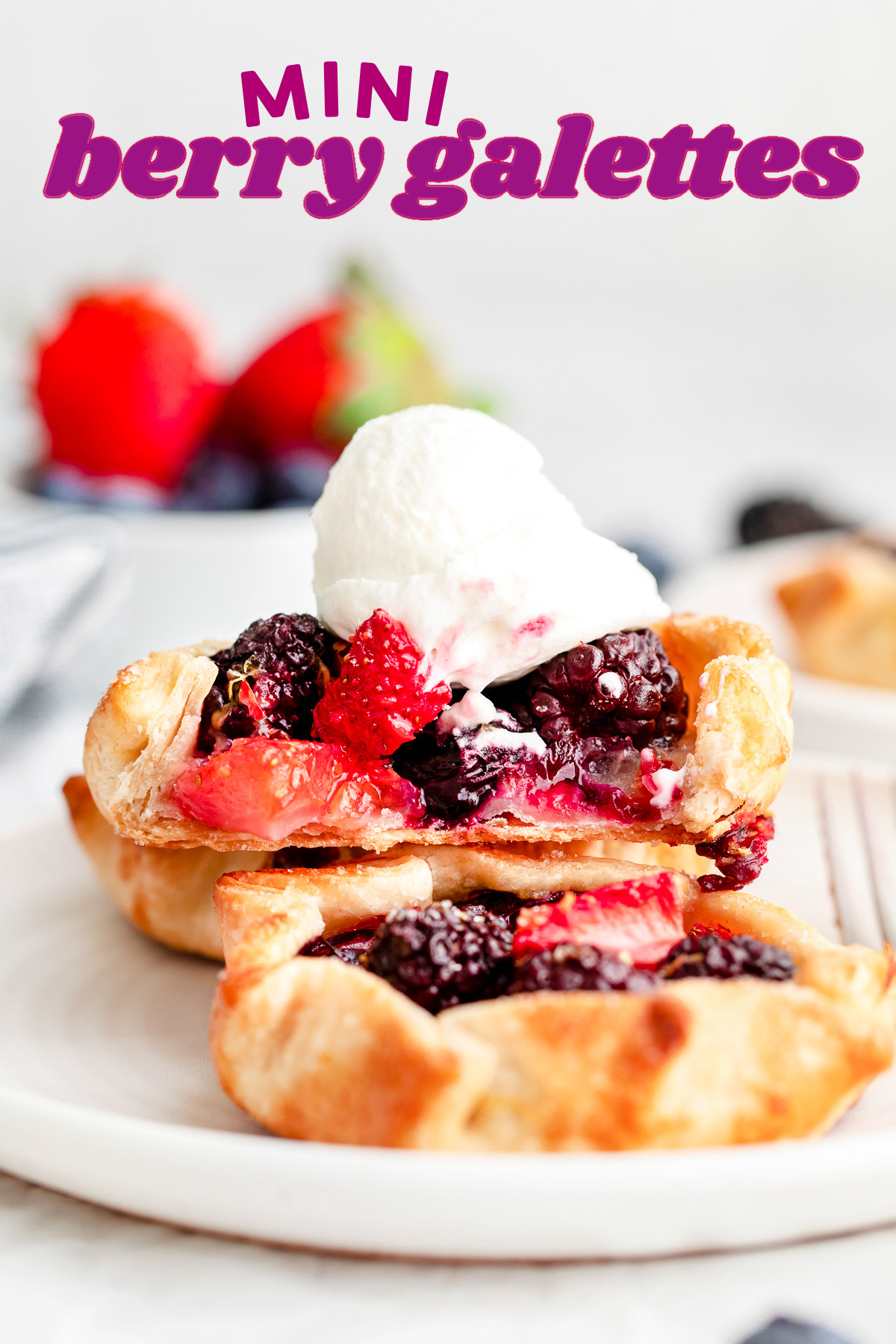 three mini berry galettes on small white plate topped with whipped cream. title overlay at top of image.