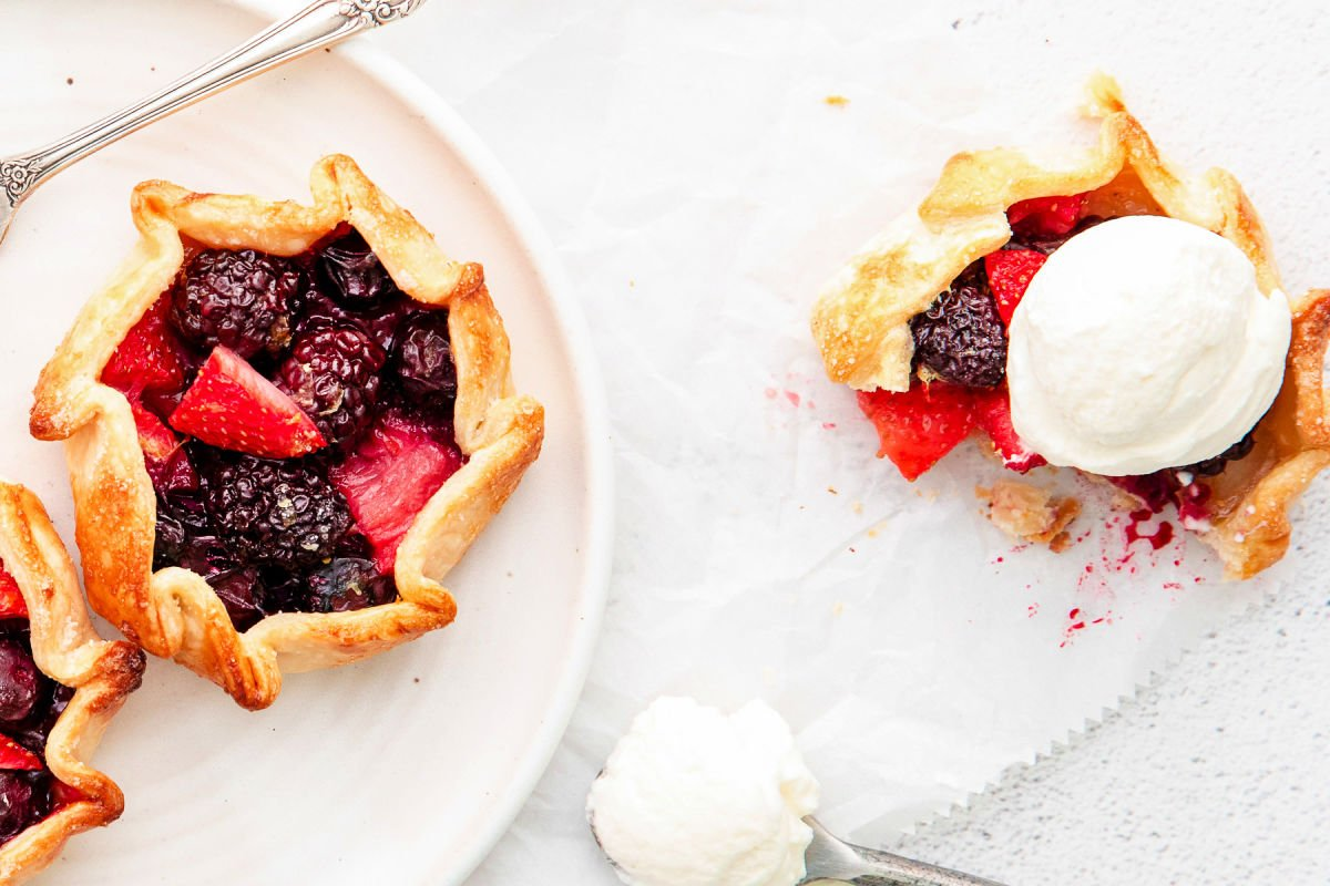 galette topped with ice cream and another berry galette sitting on white plate next to it.