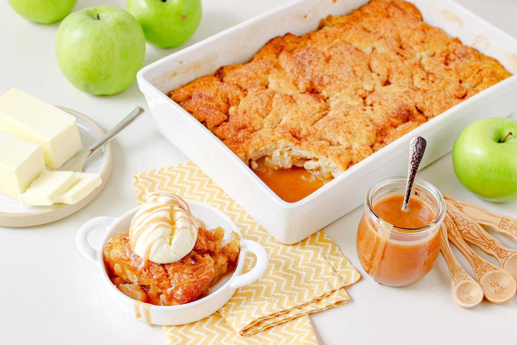 apple cobbler in large white baking dish with caramel sauce jar off to the side and green granny smith apples next to it. serving in small white bowl topping with ice cream and caramel sauce.