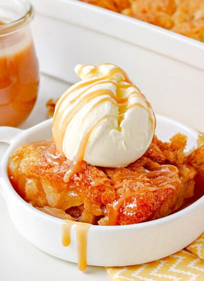 apple cobbler made with caramel sauce in small white dish topped with ice cream and salted caramel.