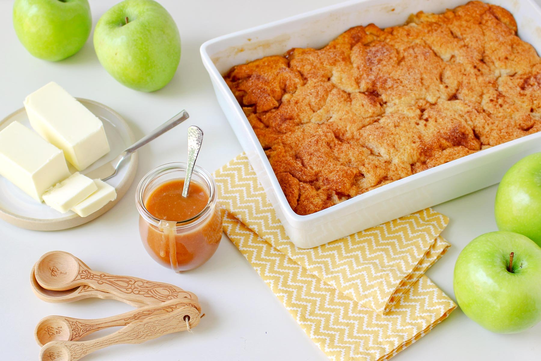 apple cobbler in large white baking dish with caramel sauce jar off to the side and green granny smith apples next to it.