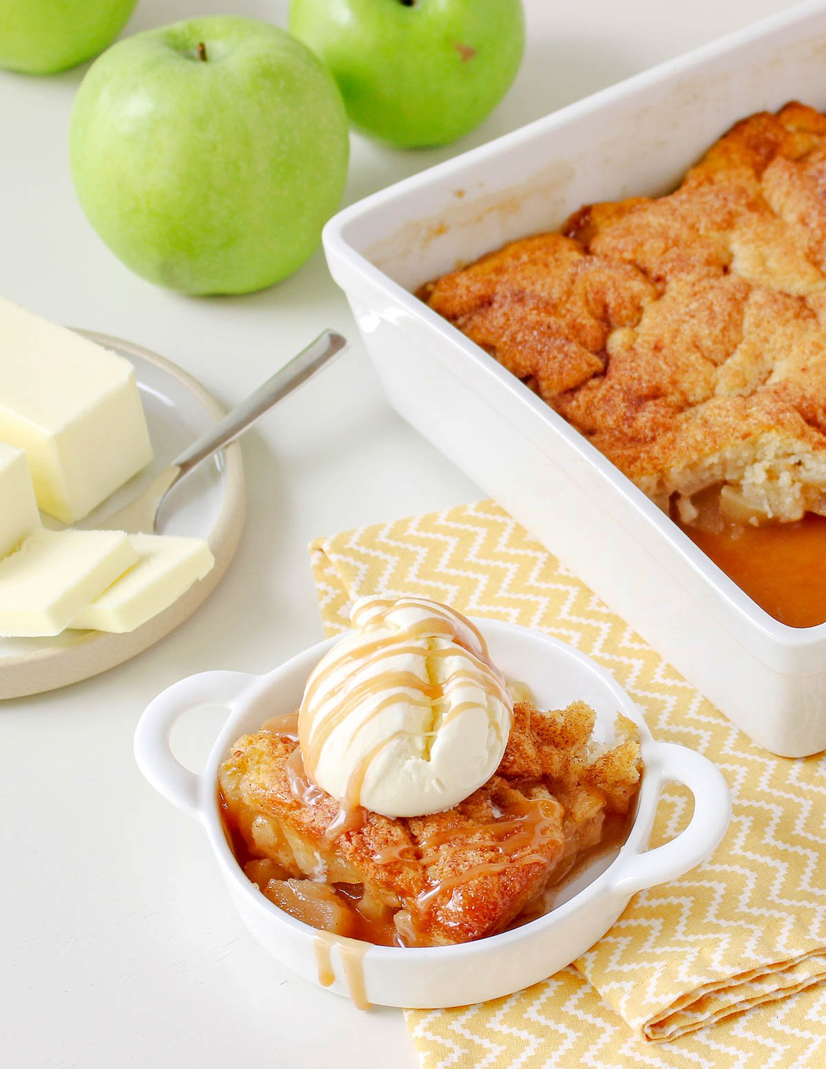 caramel apple cobbler topped with ice cream and caramel sauce near baking dish and plate of butter.